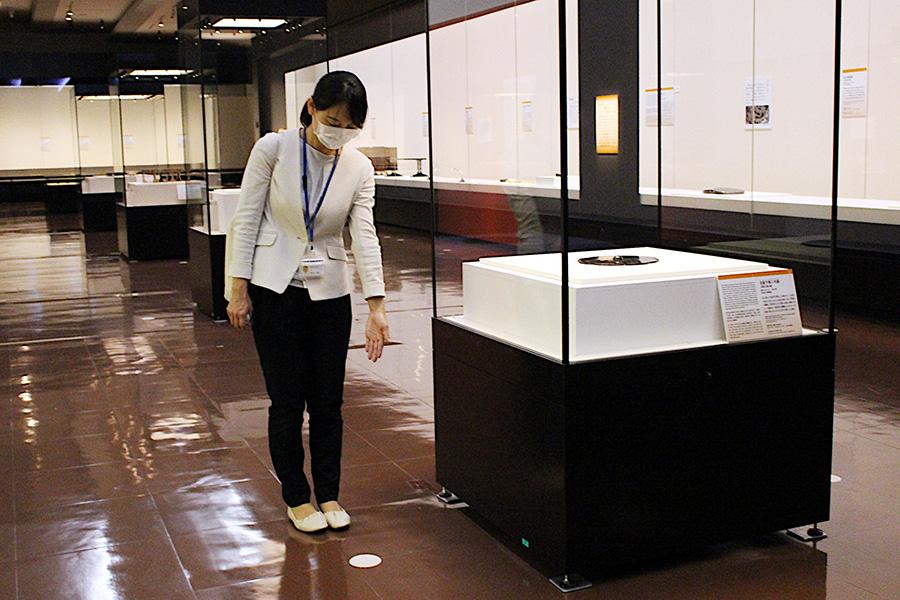 「奈良国立博物館」では、足元サインを用意し、入館制限しながら3密を避ける対応をおこなう(説明する本展担当の中川あや学芸員)