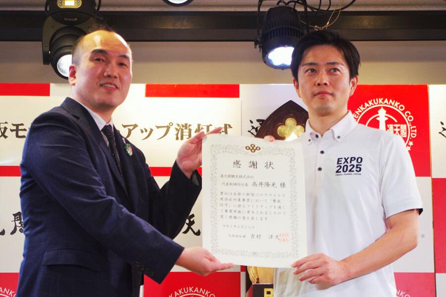 吉村知事(右)から感謝状を受け取った高井社長(6月30日・大阪市)