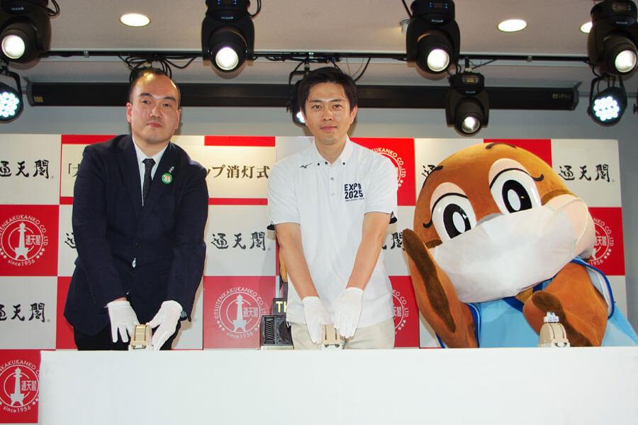 消灯式でともにスイッチを押した高井社長(左)と吉村知事、もずやん(6月30日・大阪市)