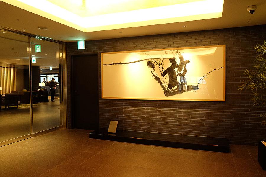 ホテル入り口のエスカレーターを昇ると、書家・川尾朋子さんの書アートが目の前に