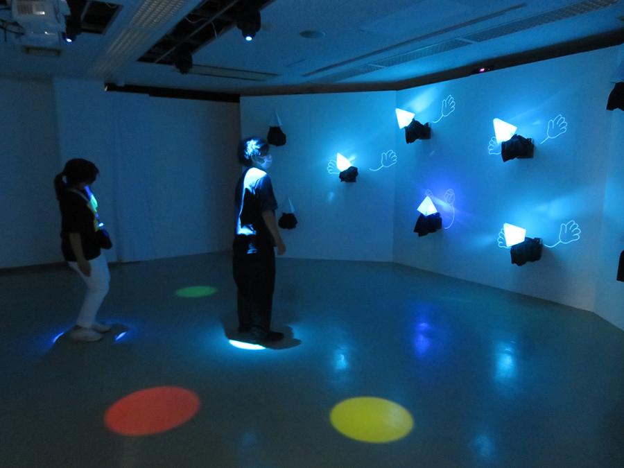 本多大和《メイト》2019年 床に投影された5色の円の上に立つと向かい壁面にメイト(仲間)が登場し、観客の動きに対応してリアクションを取る
