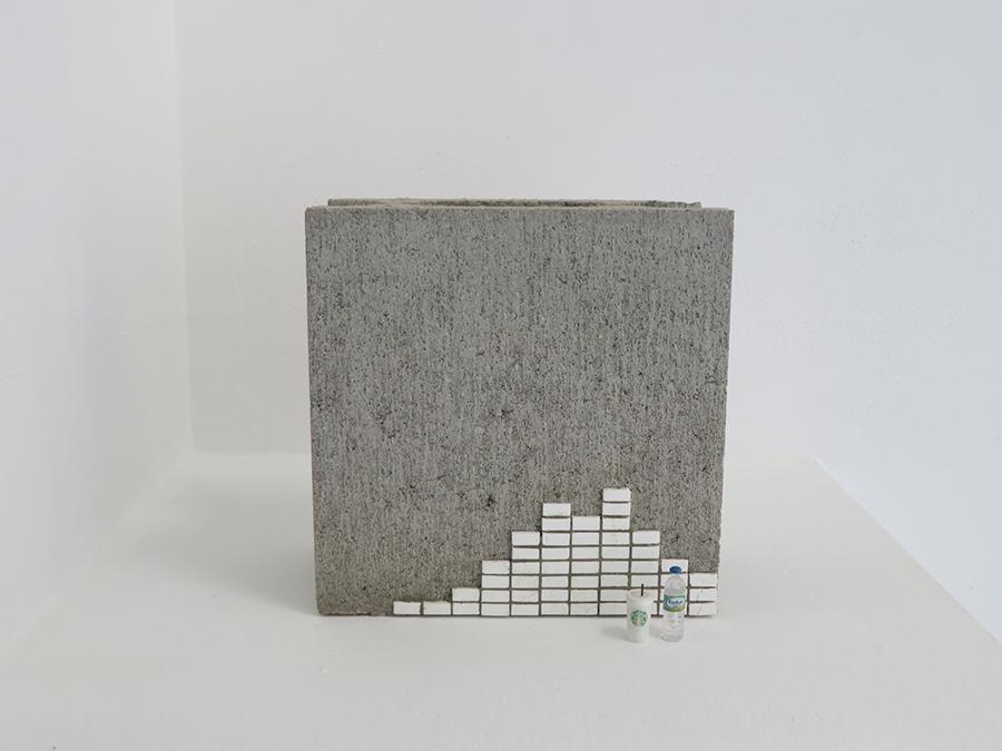 上坂直《所在譚》2019年 都市の一隅で起こった小さな物語の断片を、コンクリートブロックを背景にしてミニチュア等で表現
