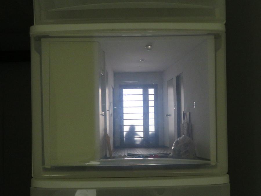 上坂直《個人的聖域・川口》2019年 積み上げた衣装ケースをアパートに見立て、室内の様子をミニチュアと映像で表現