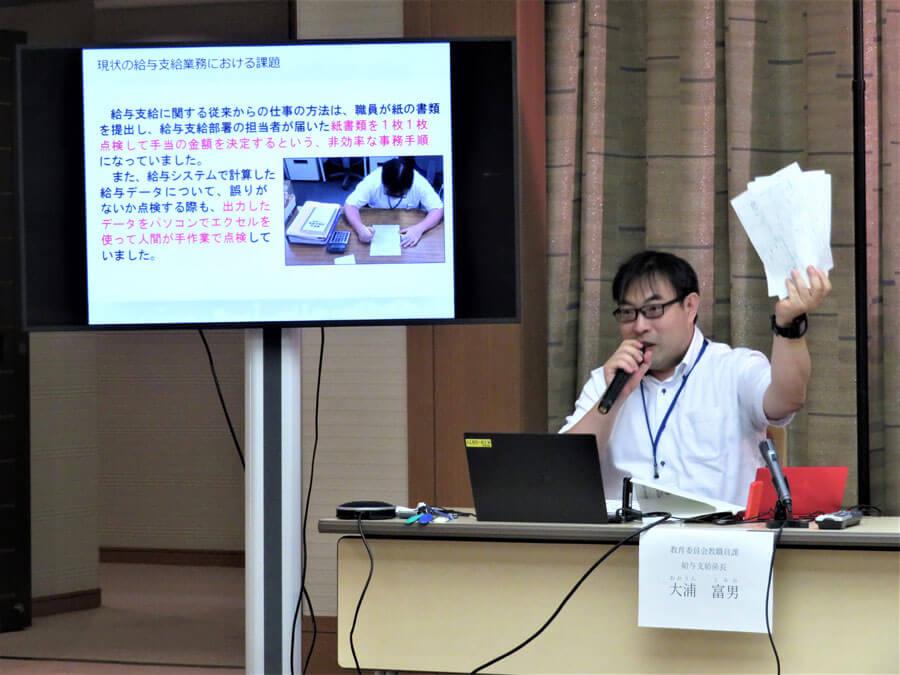 従来の手書きの申請用紙を手にする、教育委員会教職員課の大浦富男係長(8月26日・神戸市役所)