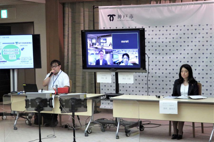 プロジェクトに関わった4者。会場には神戸市の大浦係長(左)とママスクエアの田中恵美子さん。画面は左からハニカムの大和毅社長、モンスター・ラボの押田光雄さん(8月26日・神戸市役所)