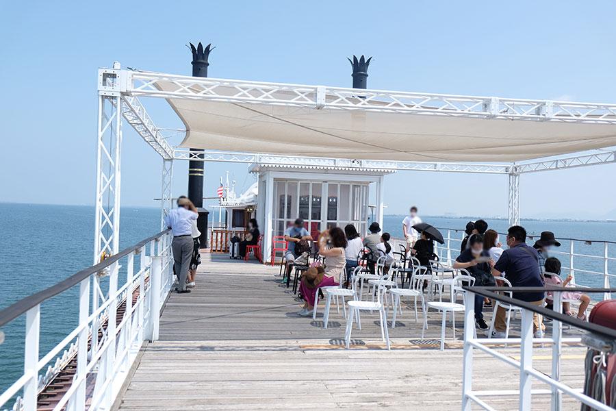 眼前に広がる湖上のパノラマを船上デッキから眺める乗船客