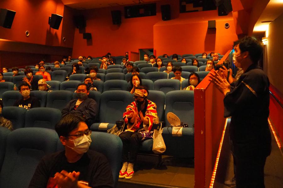 拍手のなか、甚平姿で挨拶する、映画営業部の戸村文彦さん(右端)。客席は感染予防対策で、1席ずつ空けての上映会となった