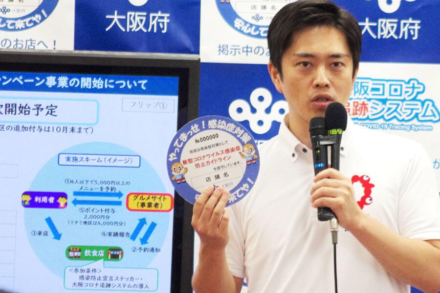 吉村洋文知事が手にするのが、防止対策に取り組んでいることを宣言する「感染防止宣言ステッカー」(9月16日・大阪府庁)