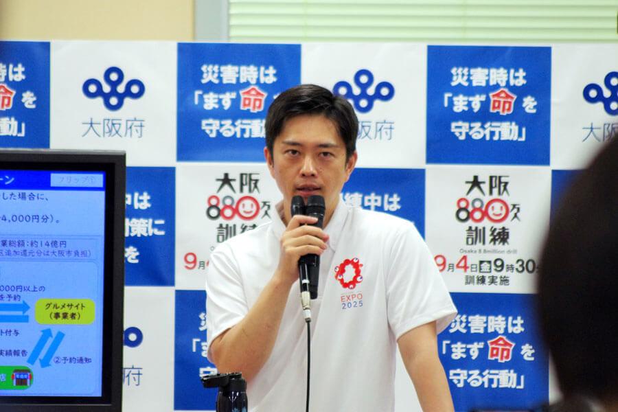 大阪・関西万博の新ロゴを胸に「食のまち大阪を盛り上げられるよう応援していきたい」と語った吉村洋文知事(9月2日・大阪府庁)