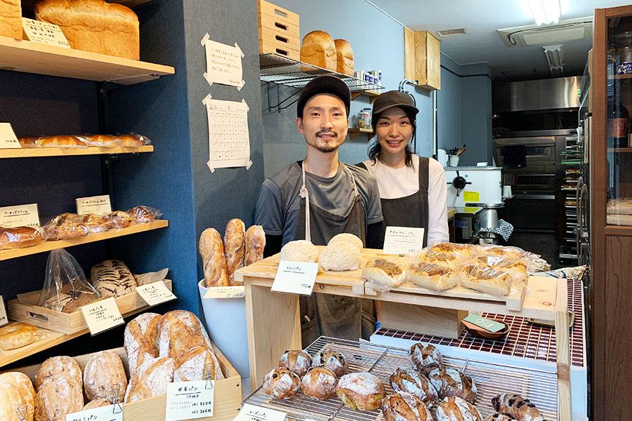 店主阪口一豊さんと奥様の麻衣子さん。店の奥の7坪と多種多様なパンを焼き上げる