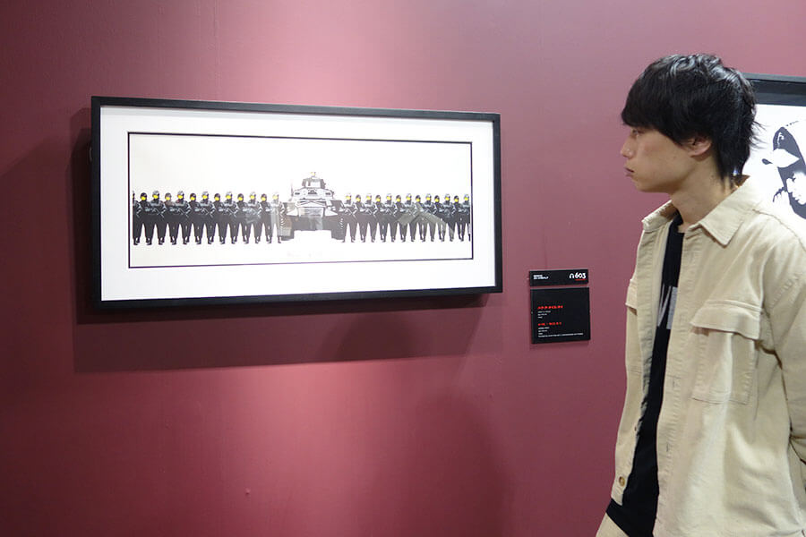 顔はニコちゃんマークなのに、手には銃。戦争についてアートを通じて問い続けるバンクシーらしい作品「ハブ・ア・ナイス・デイ」