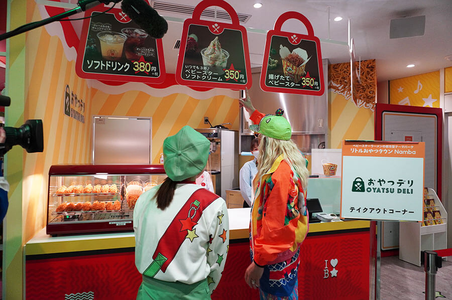 ベビースターを揚げている様子を見学するDJ KOO。「おやつデリ」ではテイクアウトメニューを販売