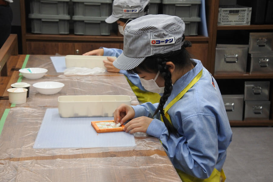 「キッザニア甲子園」に新しく登場したパビリオンで集中してDIY作業をする参加者の女の子
