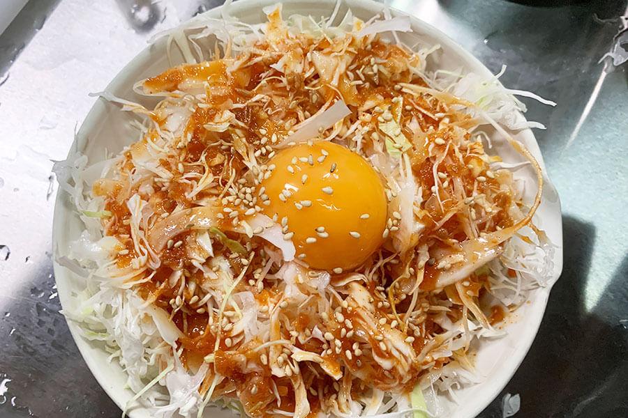 タレと卵黄を落とした千切りキャベツ。釜山ではお馴染みの肉の供