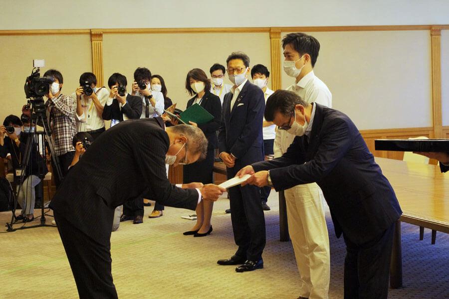 大阪市の松井一郎市長(右)から辞令が手渡された大阪港湾局の田中利光局長(10月1日・大阪市役所)