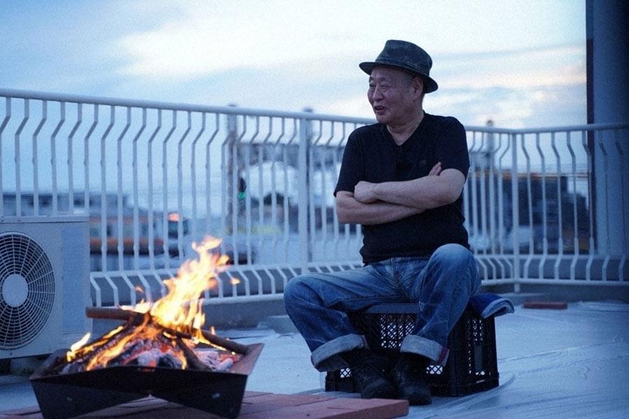 ビルの屋上で、焚き火を前に想いを語る泉谷しげる(C)NHK