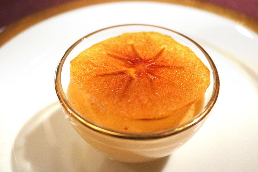 「完熟柿ミルクプリン」。火をいれるとエグみがでるという柿を、パティシエの繊細な技術でプリンに。柿のスライスをオーブンでパリパリに焼いた柿チップをトッピング