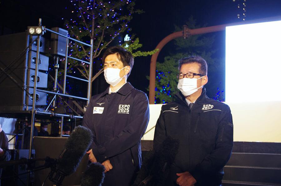 『大阪・光の饗宴2020』の開宴式終了後、囲み取材に応じた吉村洋文知事(左)と松井一郎市長(11月3日18時頃・大阪市内)