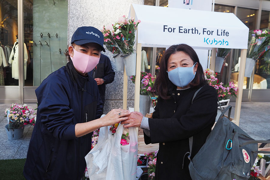 「淀屋橋odona」前で花を受け取る女性(6日・大阪市内)