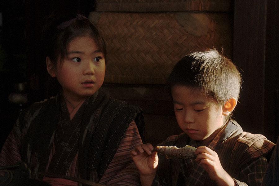 小林家で一緒にご飯を食べる千代(毎田暖乃)とヨシヲ(荒田陽向) (C)NHK
