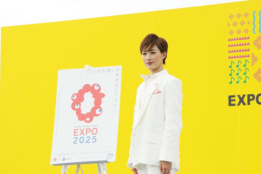 『大阪・関西万博』のポスター横で、報道陣の記念撮影に応える聖乃あすか