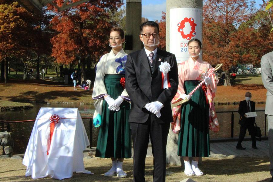 「花博記念公園鶴見緑地」に植樹された桜に、聖乃あすかが松井市長らとともに土をかけて祝った
