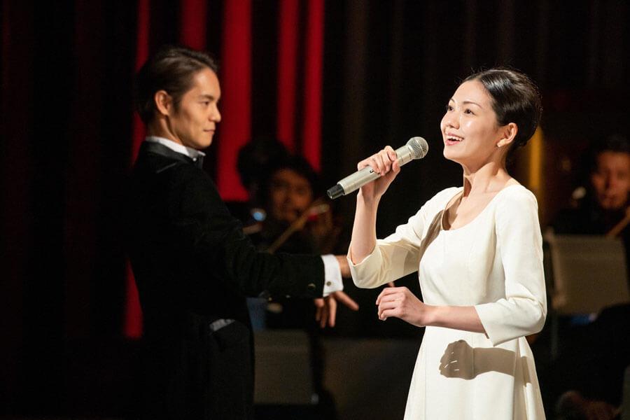 夢を実現すべく「NHKホール」の大舞台で歌う音(二階堂ふみ)と指揮をふる裕一(窪田正孝) (C)NHK