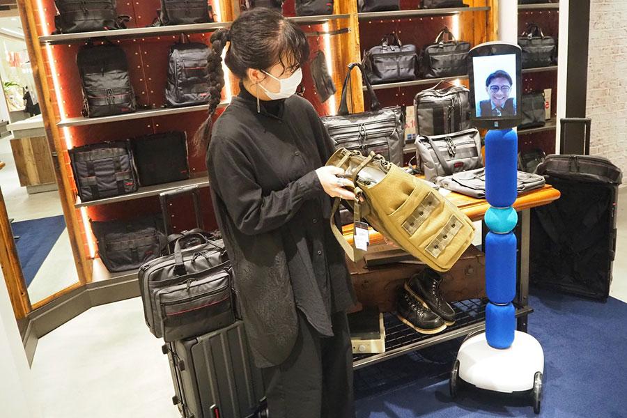 客が遠隔操作するアバターロボット「newme」の買い物風景(イメージ)。「なんばパークス」内の「BRIEFING」にて実施中