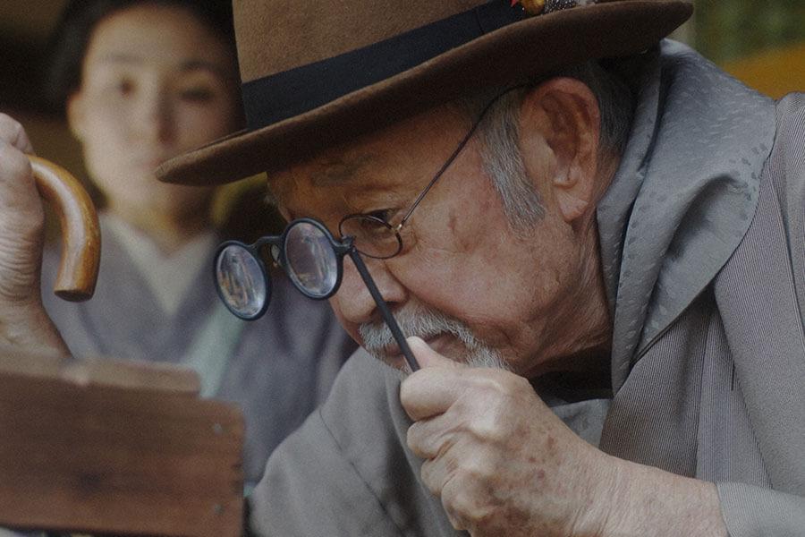 鋭い眼光で鶏を見極める峰岸社長(佐川満男)(C)NHK