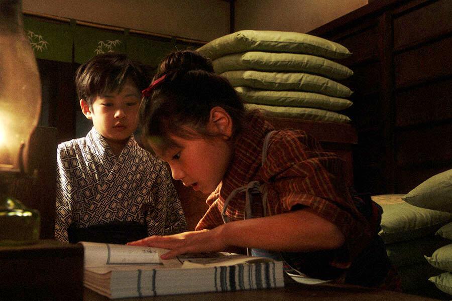 岡安・お茶子部屋裏にて。一平(中須翔真)に漢字にルビをふってもらった台本を読む千代(毎田暖乃) (C)NHK