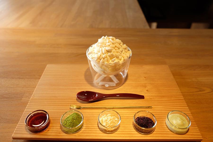「AWOMB烏丸本店」で提供していた甘味「白米ソフトクリーム」(800円)は、ポン菓子をソフトクリームにトッピングして寿司飯をイメージ。北海道産牛乳を使用した濃厚な味わいを引き立たせる、みたらし餡、抹茶、きなこ、ゆかり、泡わさびの5種を好みでかけていただく