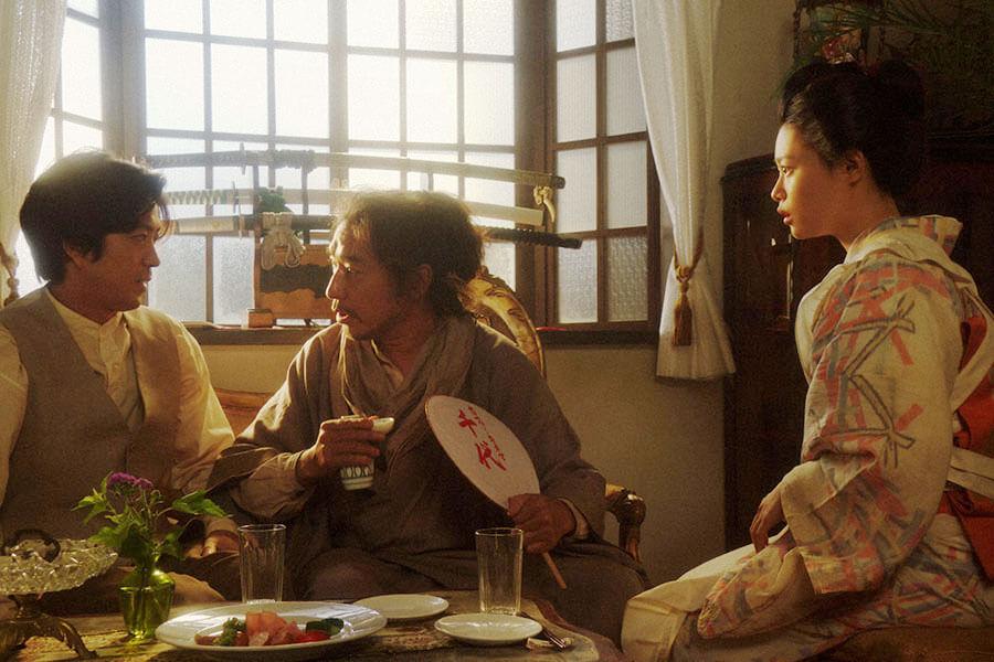 カフェー「キネマ」の店内で、千代(杉咲花)と小暮真治(若葉竜也)と一緒に話しをする竹井テルヲ(トータス松本) (C)NHK