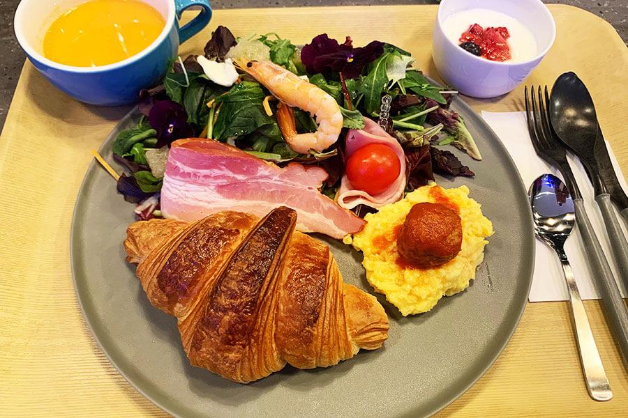 「横浜ロイヤルパークホテル」の総料理長が監修するモーニングプレート。たっぷりの葉野菜にエディブルフラワーや日替わりスープ、野菜ジュースなどがワンプレートに。クロワッサンは神戸・御影の人気店「ブーランジェリービアンヴニュ」から毎朝焼きたてが届く