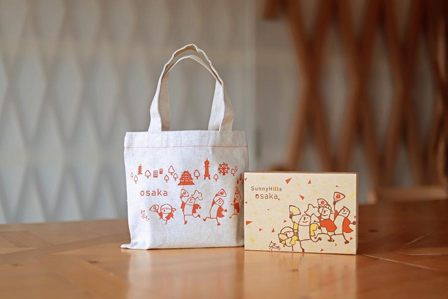 同店限定「大阪セット」(1800円)は「パイナップルケーキ」「りんごケーキ」各3個入り。キャラクターたちがどんちゃん騒ぎをする、オープン記念のパッケージも数量限定で登場