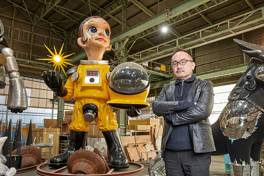 作品「サン・チャイルド」の前に立つ、現代美術作家・ヤノベケンジさん