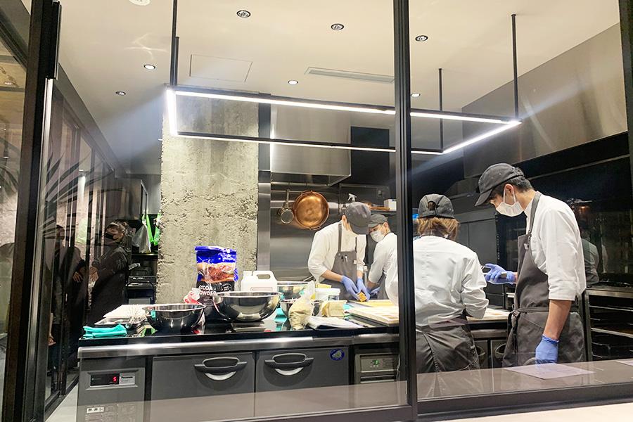 ガラス張りの厨房は足元までスケルトン。目の前の菓子作りに熱中するパティシエの真摯な姿を目の当たりにできる。「メンバーも見られることで意識が高くなり、自覚も持てるようになると思います」と広報担当の赤座祥子さん