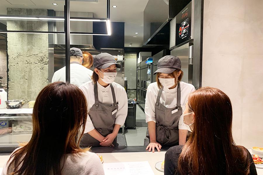 厨房のガラス窓を開けて、お客との会話を楽しむ森えみりさん(右)と野中優希さん
