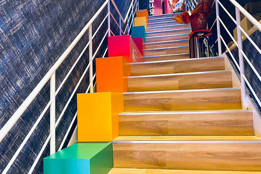 階段横のカラフルな段差には「SIT DOWM」の文字