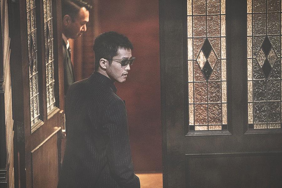 背後を気にしながらどこかに入ってゆく日岡(松坂桃李)(C)2021 「孤狼の血 LEVEL2 」製作委員会