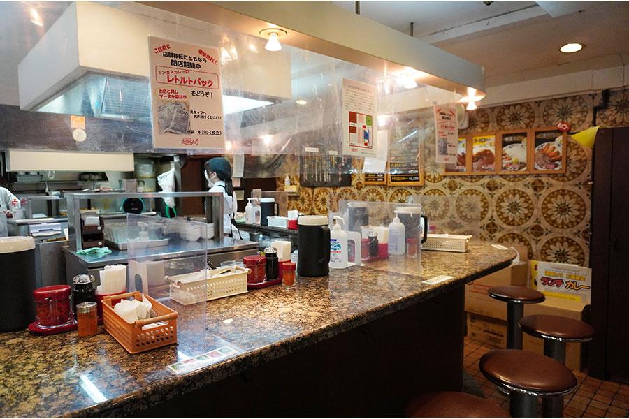 レトロなモザイク風壁や重厚感のあるテーブルが特徴の店内
