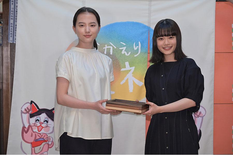 『おちょやん』の主演・杉咲花(右)へ、『おかえりモネ』の主演・清原果耶からお盆のプレゼント。後ろにかかるのは杉咲からの贈り物であるのれん(5月6日・提供:NHK大阪)