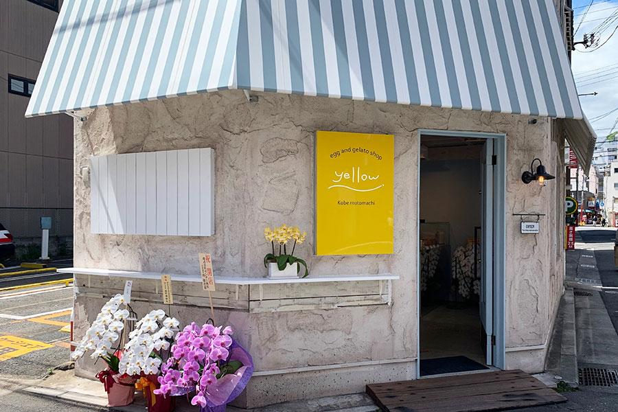 白&グルーグレイのテントと卵黄のシンボルカラー・黄色の看板が目印