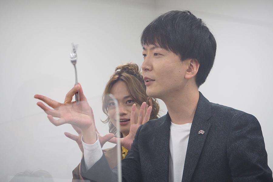 開口一番、「ご挨拶代わりといってはなんですが…」と、フォークを使ったマジックを披露し、取材陣を圧倒した新子。後ろで主演俳優・池田も力添え?(25日、大阪市内)