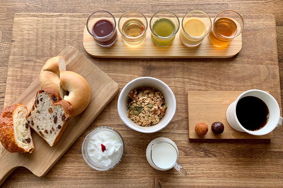 宿泊者のみの朝食セット。アサイーやクコの実、モリンガ、サジーなどスーパーフードを使った5種のドリンク、自家製グラノーラ、日替わりでお取り寄せのパンなど。添加物、グルテン、白砂糖フリーのブリスボールはオーストラリア発祥の加熱しないお菓子でテイクアウトもできる。