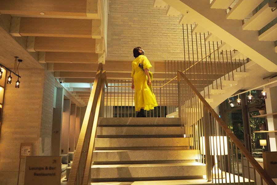 黄色のドレスを着て、ホテル内を散策する先輩女性記者