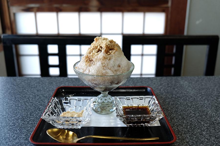 """新作「沖縄ぜんざい」(800円)には金時豆を黒糖でほっくり煮た""""沖縄版あずき""""と白玉を足元にしのばせて。黒糖を煮詰めた純粋なシロップときな粉を好みでトッピングする"""