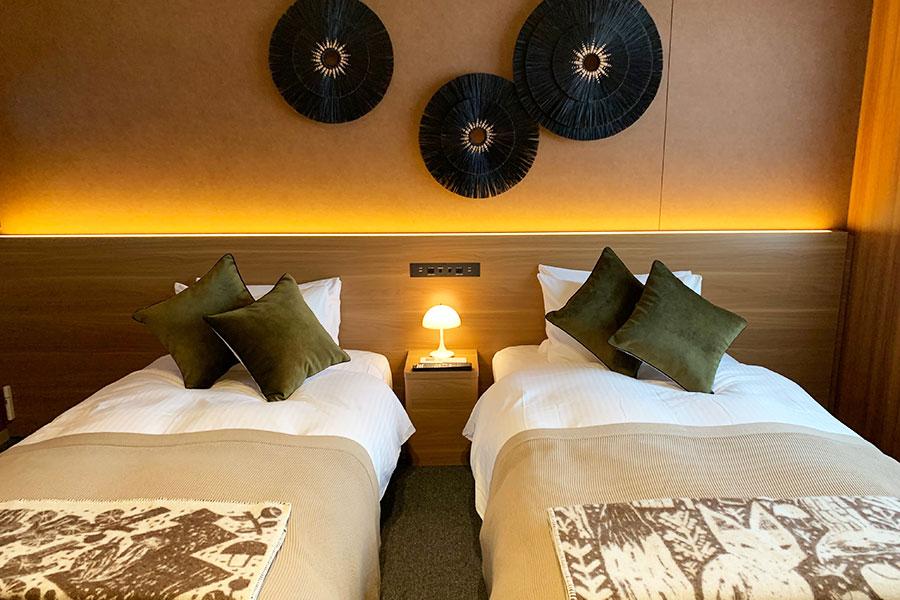 「プレミアムルーム」1003号室。「川端滝三郎商店」ならではのしつらえに。ブランケットやクッションもかわいいベッドルーム