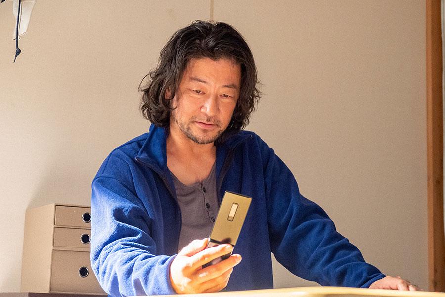 携帯電話を見つめる新次(浅野忠信)(C)NHK