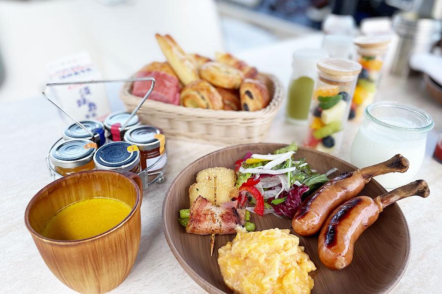朝食は屋上のテラスデッキでグランピング・モーニングを堪能。淡路島の旬の食材を贅沢に使ったクルーザー宿泊客専用メニューでゆっくりと朝食を。焼き立てクロワッサン含む5種類のパンに骨付きソーセージや鱧のフライなど盛りだくさん