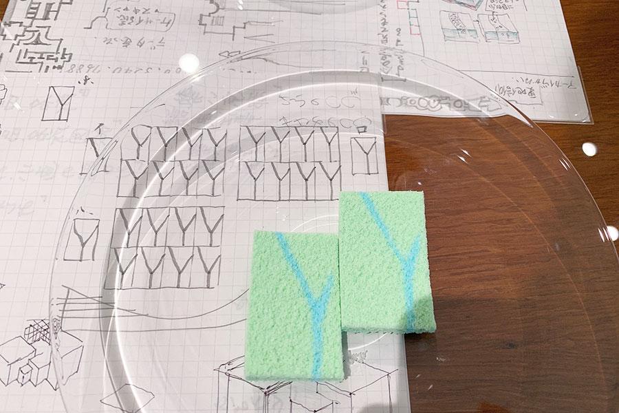 山口氏による落雁うつろひ「下鴨」。「下鴨あたりのやさしい緑とせせらぐ水をイメージ」したそうで、「鴨川デルタ」と呼ばれる出町柳の三角州が表現されている。お菓子と合わせて山口画伯のアイデアスケッチも展示